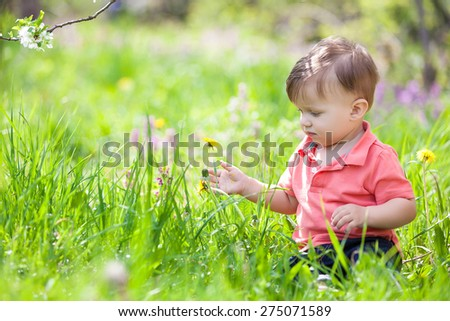 Portrait of adorable little boy in a blossom tree garden, positive emotions, smiling - stock photo