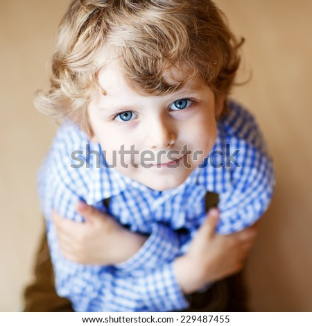 Portrait of adorable little boy with blond hairs and blue eyes, indoor. - stock photo