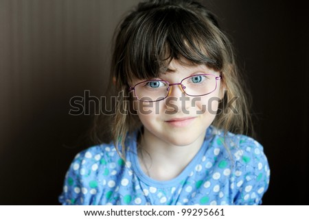 Portrait of adorable little brunette girl in spectacles on dark background - stock photo