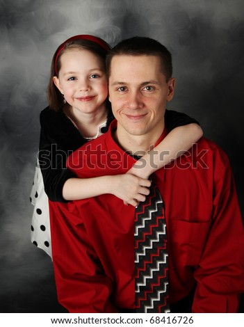 Portrait of adorable little girl and handsome father in dressy clothing hugging - stock photo