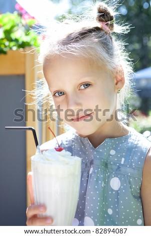Portrait of adorable little girl drinking fresh milkshake - stock photo