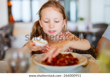 Portrait of adorable little girl eating lunch at restaurant - stock photo