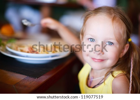 Portrait of adorable little girl having lunch - stock photo