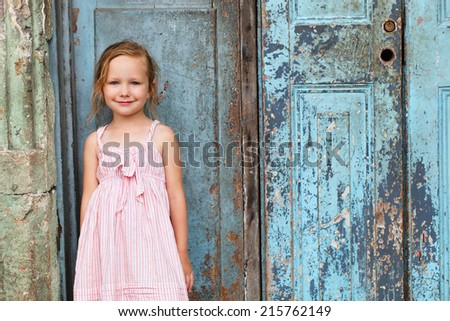 Portrait of adorable little girl outdoors on a street against old door - stock photo
