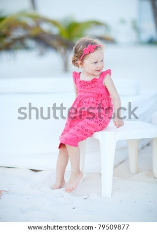 Portrait of adorable little girl sitting at white sand beach - stock photo