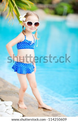 Portrait of adorable little girl standing near a swimming pool