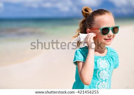 Portrait of adorable little girl with a seashell