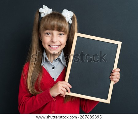 Portrait of adorable little girl with small blackboard at the black chalkboard in classroom.  - stock photo