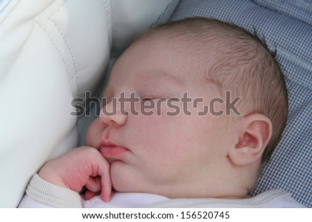 Portrait of adorable new born one week old baby sleeping peacefully in stroller