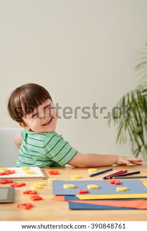 Portrait of adorable preschool boy studying at home