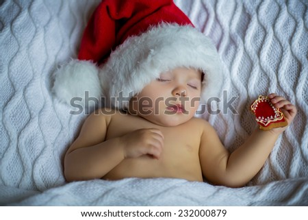 portrait of adorable quite beautiful girl sleeping in christmas hat on white blanket with bitten cookie in her hand - stock photo