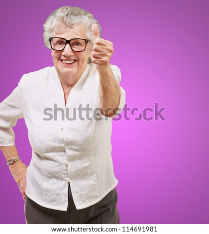 portrait of adorable senior woman doing good gesture over purple background - stock photo