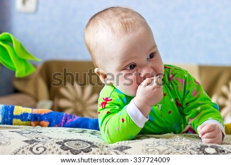 Portrait of adorable serious baby boy eating cabbage - stock photo