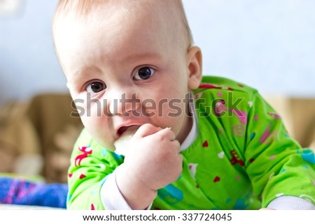 Portrait of adorable serious baby boy eating cabbage and looking at camera. Close up - stock photo