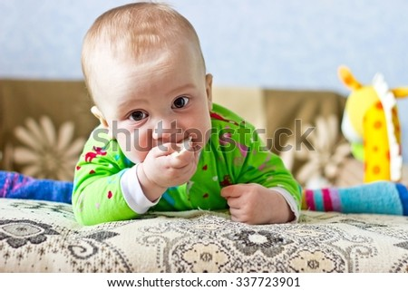 Portrait of adorable serious baby boy eating cabbage and looking at lens. Horizontal image - stock photo