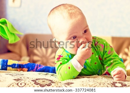 Portrait of adorable serious baby boy eating cabbage. Image with vintage filter - stock photo