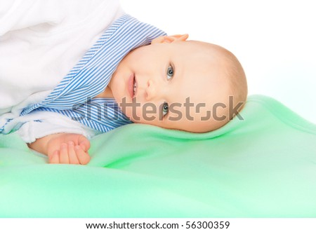 Portrait of adorable small baby boy in bathrobe lying on green towel