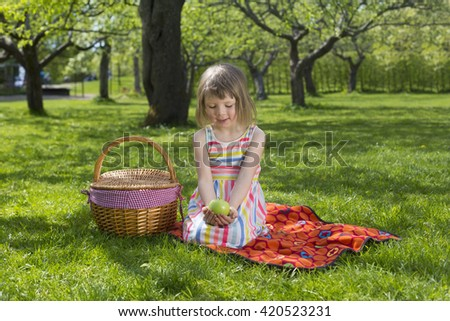 portrait of adorable small blond girl in preschool age siting with picnic basket and green apple outdoors on green meadow - stock photo