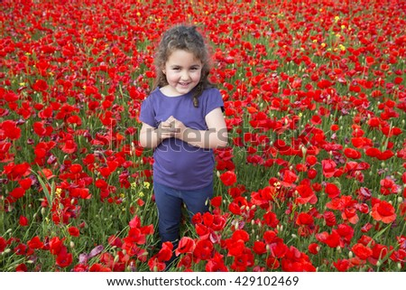 Portrait of adorable smiling girl with brunette curly hair looking at camera in red flowers field - stock photo