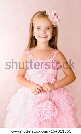 Portrait of adorable smiling little girl in princess dress with her handbag - stock photo