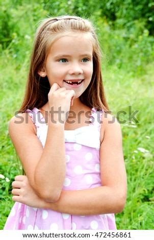 Portrait of adorable smiling little girl in summer day outdoor