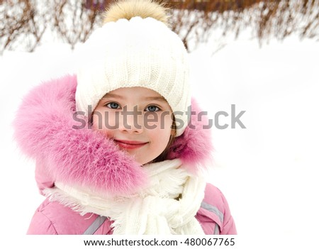 Portrait of adorable smiling little girl in winter day outdoor