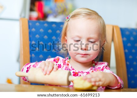 Portrait of adorable toddler girl helping at kitchen