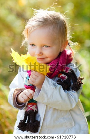 Portrait of adorable toddler girl with yellow leaf