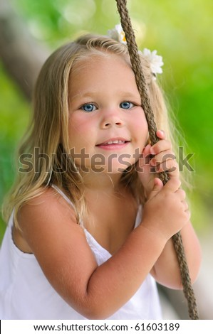 Portrait of adorable toddler smiling girl with flower on her hair - stock photo