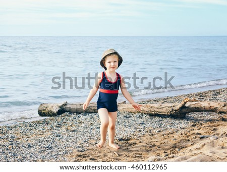 Portrait of adorable white Caucasian one toddler little girl with hat on her head going on lake sea gravel beach, emotional face expression, lifestyle summer mood - stock photo