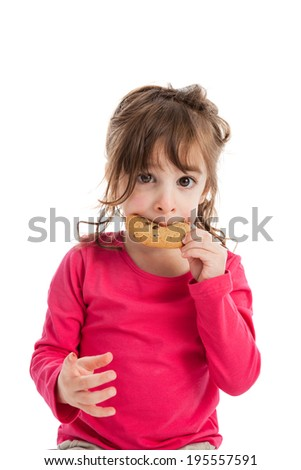 Portrait of adorable 3 year old girl eating a chocolate chip cookie isolated on white background - stock photo