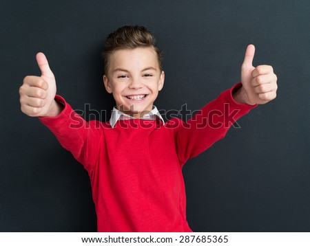 Portrait of adorable young boy showing thumbs up sign using both hands at the black chalkboard in classroom. - stock photo