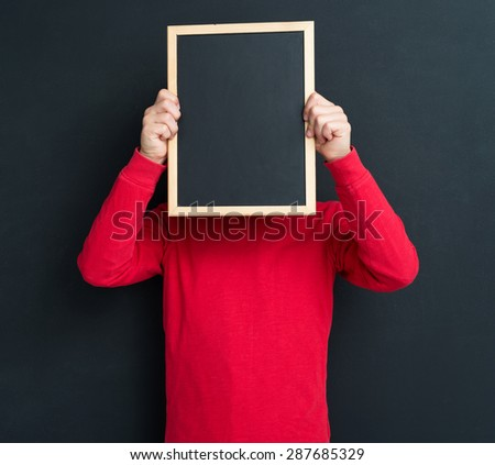 Portrait of adorable young boy with small blackboard at the black chalkboard in classroom.  - stock photo