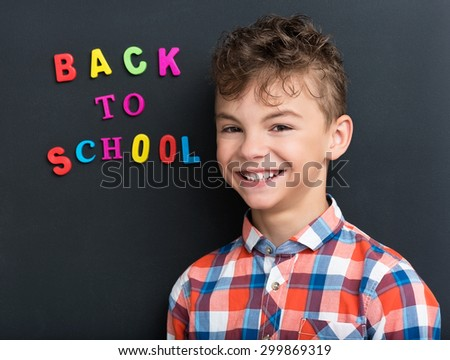 Portrait of adorable young boy 11 years old posing at the black chalkboard in classroom.  - stock photo