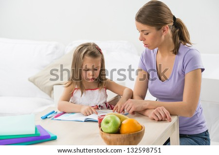 Portrait of adorable young girl and mother studying drawing at home - stock photo