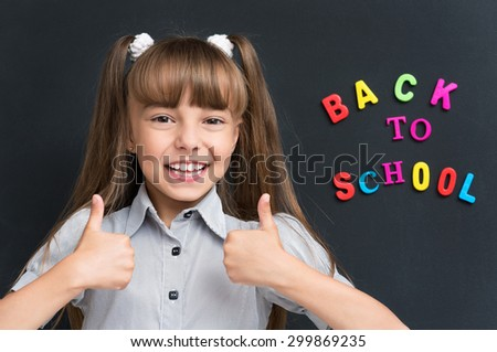 Portrait of adorable young girl showing thumbs up sign using both hands at the black chalkboard in classroom. - stock photo