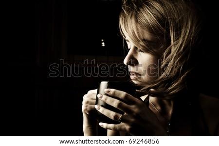 Portrait of adult attractive woman indoor in dark room drinking coffee - stock photo