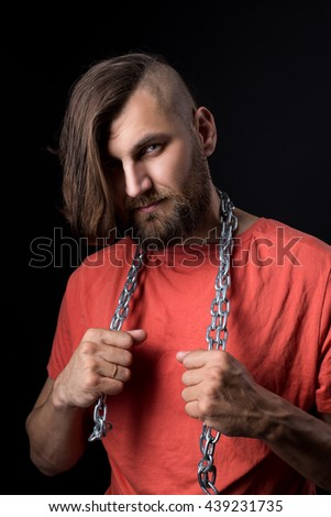 Portrait of adult bearded man with steel chain on neck looking at camera.Isolated. - stock photo
