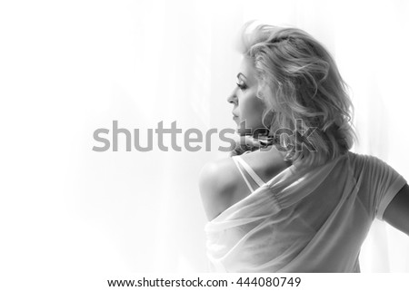 Portrait of adult blonde woman looking at window and thinking of something. Black and white photo. - stock photo