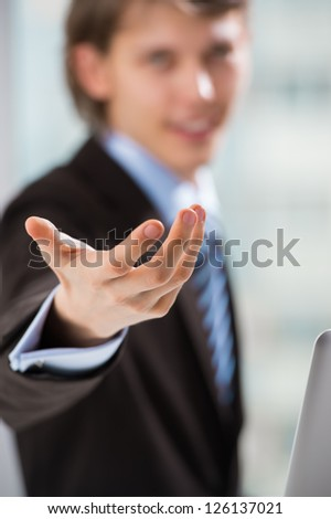 Portrait of adult business man pointing at you at his office