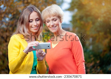 Portrait of Adult caucasian daughter showing on mobile phone to her senior mother outdoor in nature - stock photo