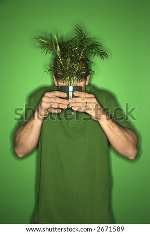 Portrait of adult Caucasian man on green background holding plant in front of his face. - stock photo