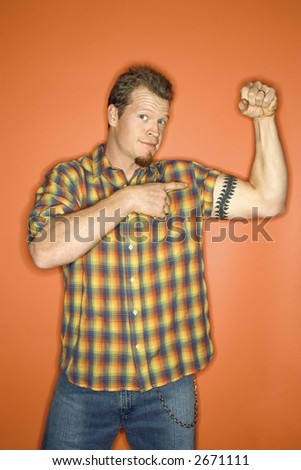 Portrait of adult Caucasian man on orange background flexing and showing off his arm muscle. - stock photo