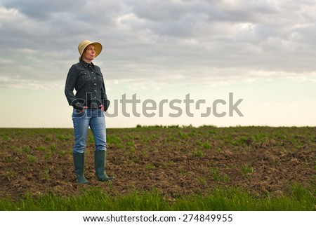 Portrait of Adult Female Farmer Standing on Fertile Agricultural Farm Land Soil,Looking into Distance. - stock photo