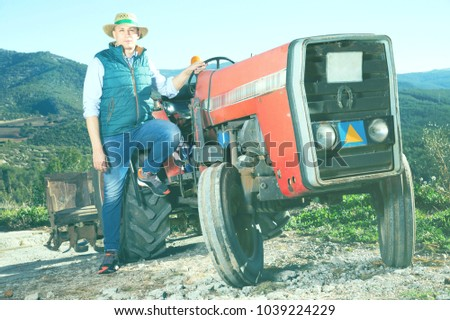 Portrait of adult glad cheerful positive male farmer near tractor on background with large vineyard