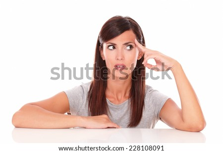 Portrait of adult hispanic woman wondering while looking to her left on isolated white background - copyspace - stock photo