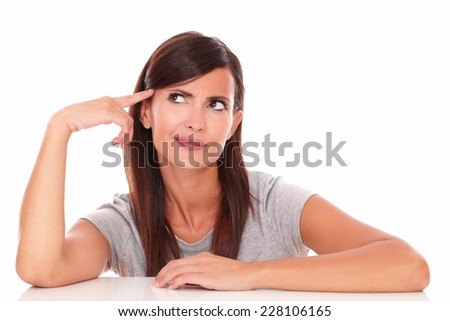 Portrait of adult lady on grey t-shirt wondering while looking up on isolated white background - copyspace - stock photo