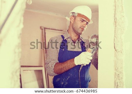 Portrait of adult male constructor with circular saw in gloves, helmet and workwear