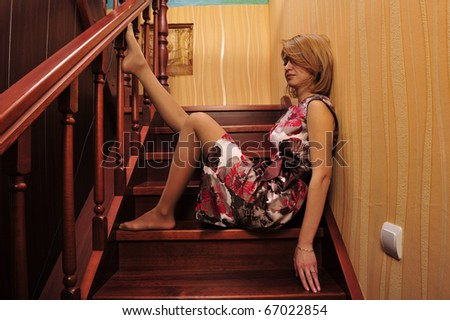 Portrait of adult tired woman sitting on stairs and thinking about something - stock photo