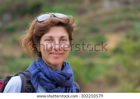 Portrait of adult woman looking at camera, with green eyes and cheerful facial expression. Concept of traveling backpackers and adventures. Natural daylight, natural skin, shot outdoors. - stock photo